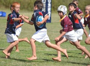 Boys playing rugby barefoot
